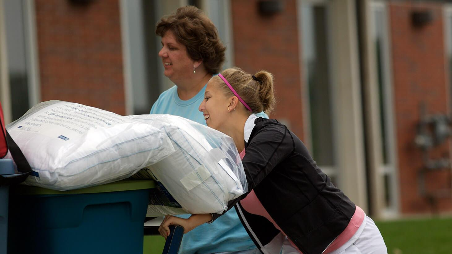 Student pushing cart during move in