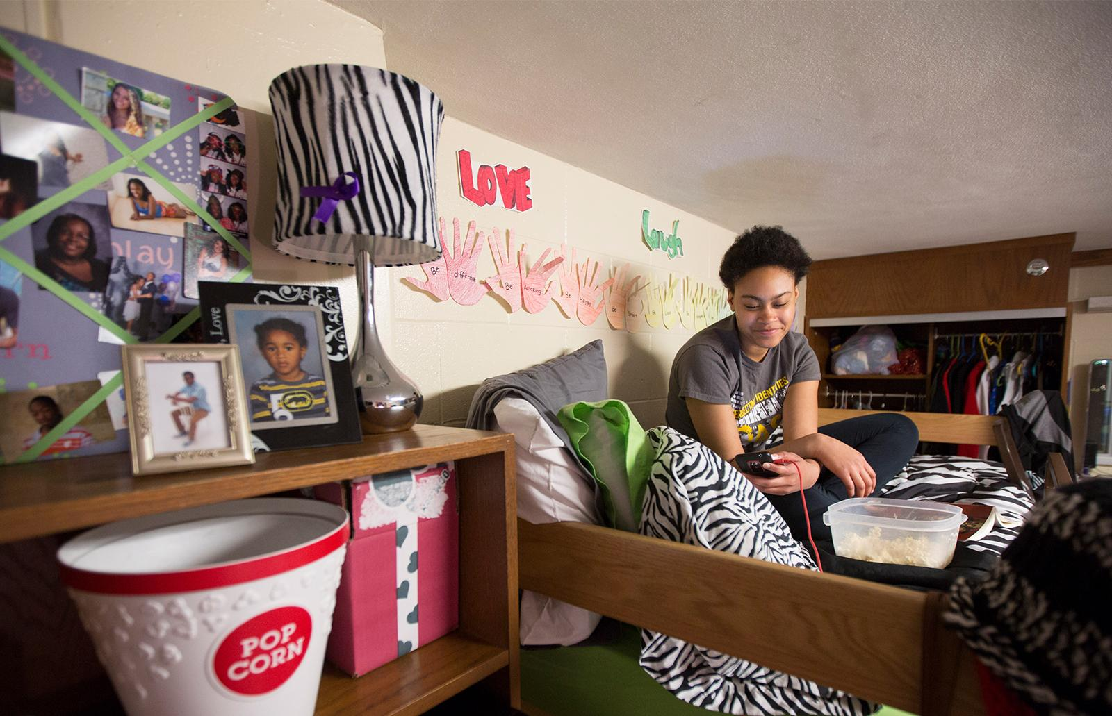 Student sitting on bed in room and texting
